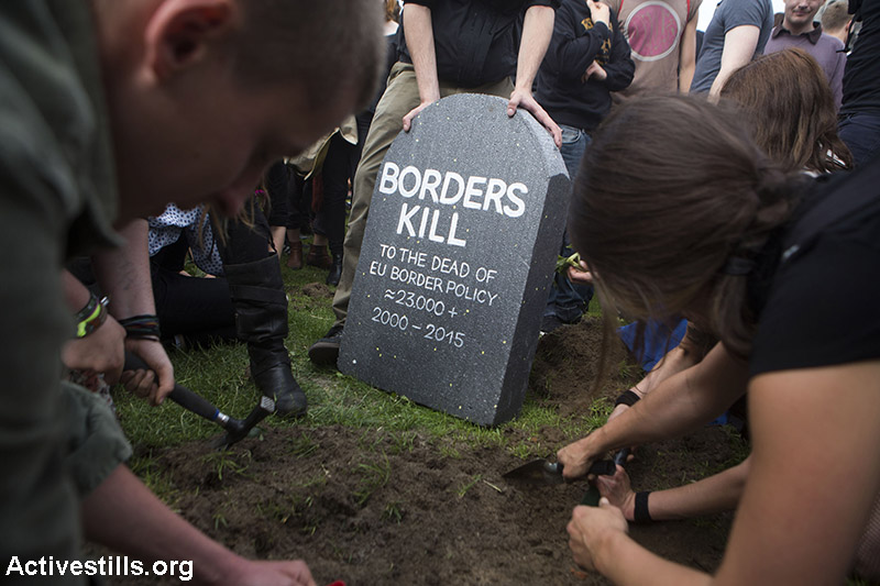 """Activists dig mock graves in front of the Reichstag during a march and action in solidarity with migrants and refugees, Berlin, Germany, June 21, 2015. Thousands protested against European restrictive migration policies under the slogan """"Refugees are welcomed here"""". Activists stormed the fences around the Reichstag field and dug dozens of symbolic graves to commemorate thousands of migrants who died on their way to Europe. This action was part of a campaign """"die toten kommen"""" (the dead are coming) organized by the Center for Political Beauty, a Berlin-based art activist group. (Activestills.org)"""