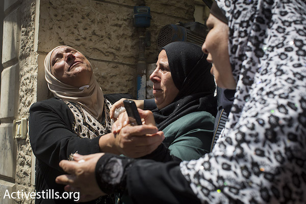 An aunt of Muhammad Abu Latifa cries at his funeral in Qalandia Refugee Camp in between Ramallah and Jerusalem, July 27, 2015. Abu Latifa was killed while fleeing Israeli special police commandos during an arrest raid on his home early that morning. (Oren Ziv/Activestills.org)
