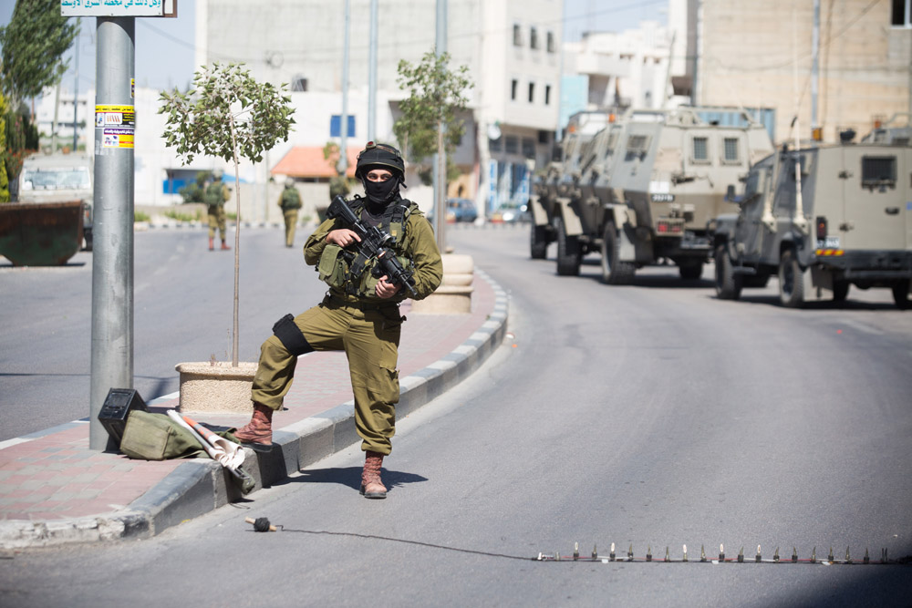 Flying checkpoints can show up without any warning, and often times separate Palestinians cities and towns. (Photo by Activestills.org)