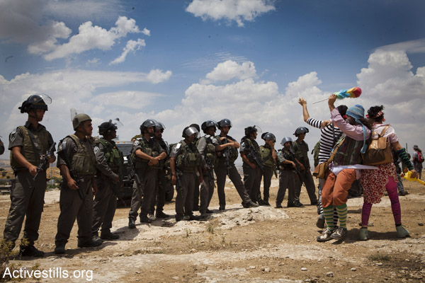 Members of the 'Clown Army' confront Israeli security forces during a solidarity protest in the Palestinian village of Susya, June 22, 2012. (Photo by Oren Ziv/Activestills.org)