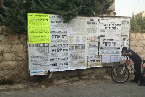 Religious Jewish youth looking at death notice for Ali Dawabshe in Jerusalem (Photo by Ilana Sichel)