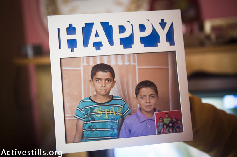 Framed photo of Ahmed Mustafa Zo'rob (15) and his brother Mohammed Mustafa Zo'rob (12), photographed in their home in Rafah on February 10, 2015. They were both killed on August 1st, 2014 during an attack on their uncle's home, together with 14 other members of their family, including their mother and two other siblings. (Anne Paq / Activestills.org)