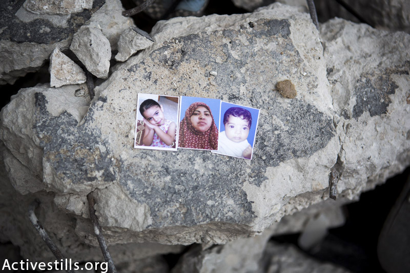 Photos of Aseel Mohammed Al Bakri (4), her mother Ibtisam Ibrahim Al Bakri (38), and her sister Asmaa (5 months), displayed in the ruins of their home, Al Shati' refugee camp, Gaza City, September 11, 2014. They were killed by an Israeli attack on their home on August 4, 2014, with two other members of their family. (Anne Paq / Activestills.org)