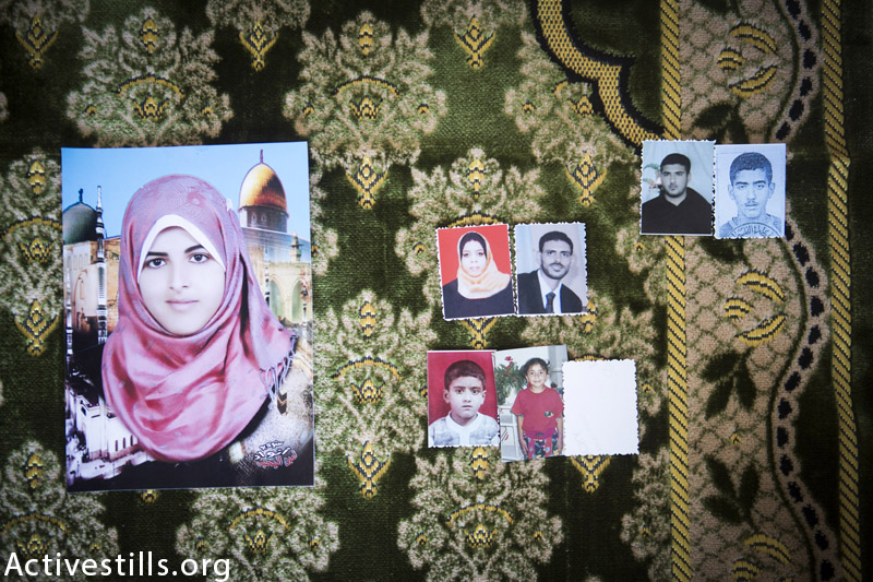 Photos of 7 members of the Al Louh family displayed  on the carpet 18-year-old Eman used (large photo on the left) when she was praying and killed, seen on September 16, 2014 in  Deir al Balah, Gaza Strip. In total, the Israeli attack which took place on 20 August 2014, killed 8 members of the Al Louh family and destroyed two of their homes. The immediate family of Ra'fat Al Louh (Ra'fat, his wife and their three children) was entirely deciminated. Eman Al Louh was hit by a piece of concrete which flew from the window and killed her while she was praying in her home located around 150 meters from the center of the attack. (Anne Paq / Activestills.org)