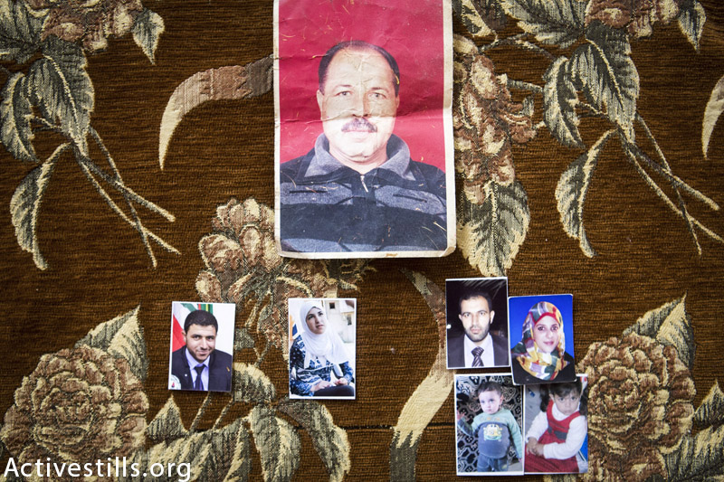 Photos of the seven members of Mohammed Atta Mahmoud Al Najjar's family seen in the home of Mohammed's brother, in Khan Younis, Gaza Strip, February 18, 2015. A total of eight members of his family were killed by an Israeli attack on his home on July 29, 2014. His entire immediate was killed: Atta (29); his wife Ibtisam (21) and their two children Mohammed (2) and Rafeef (3). Atta worked for the civilian police in Gaza. (Anne Paq / Activestills.org)