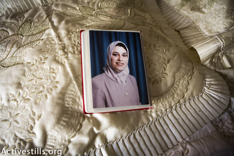 A photo of Taghrid Shabaan al Kilani is laid out on her bed in Beit Lahiya, Gaza Strip, September 18, 2014. Taghrid was killed together with her husband Ibrahim and their five children in an Israeli attack on the building to which they fled in Gaza City on July 21, 2014. Ibrahim and her children are German citizens; Ibrahim had lived in Germany for 20 years and was working there as an architect. They fled their home in Beit Layhia after the Israeli army dropped warning leaflets in their neighborhood, which urged the residents to go to Gaza City. (Anne Paq / Activestills.org)