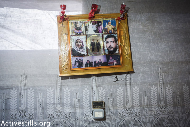 Photos of the killed members of the family of Zaki Wahdan seen in a frame in their shelter in Beit Hanoun, northern Gaza Strip, February 18, 2015. 8 members of the Wahdan family, mostly women and children were killed in an Israeli attack in their home on 22 July 2014. The attack occured after the Israeli soldiers left the home that they occupied and after they told them to stay inside the house. (Anne Paq / Activestills.org)