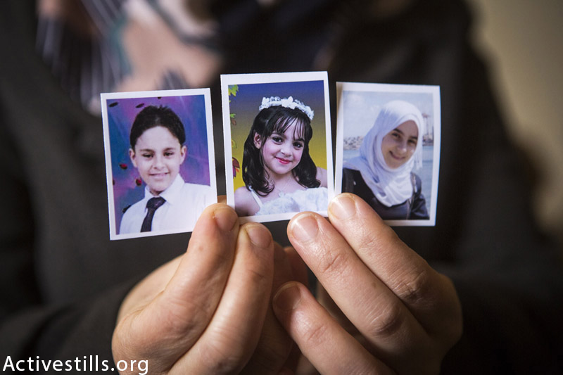 Photos (from left to right) of the killed siblings Mohammed (12), Yara (8) and Nadeen (16) Mahmoud Al Farra, held by their mother in their home in Khan Younis, February 22, 2015. Nine members of the Al Farra family were killed in the street by an Israeli missile while they were fleeing their home on August 1st, 2014. (Anne Paq / Activestills.org)