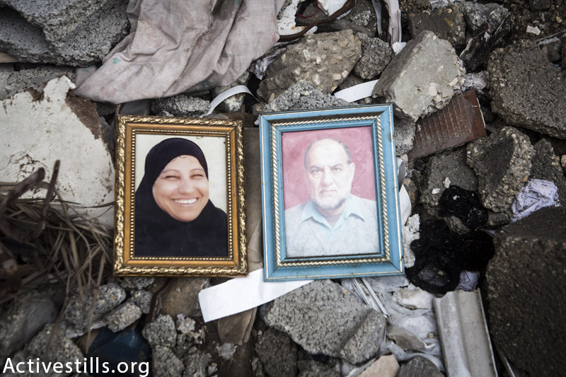Photos of Ibrahim Abdullah Abu Itta (67) and his wife Jamila (55) seen in the ruins of their destroyed home in Jabaliya refugee camp, Gaza Strip, February 23, 2015. They were killed together with two of their sons and one grandchild following an Israeli attack on their neighbours' home on July, 24, 2014. (Anne Paq / Activestills.org)