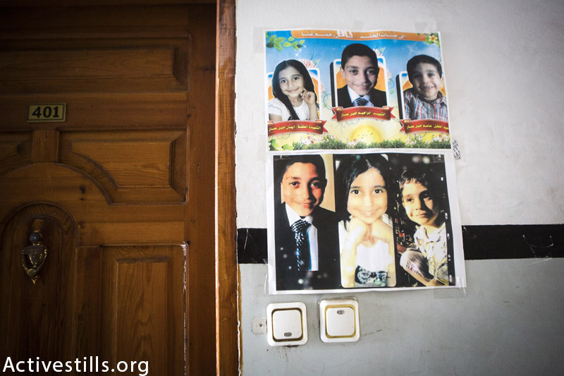Photos of the three siblings of the Ammar family who were killed in an Israeli airstrike: Eman (9); Ibrahim (13) and Issam Khalil Ammar (4), displayed on the wall next to their door of their flat in the Cordoba building, Gaza City, February 25, 2015. The three children were killed on July 20, 2014 by an Israeli attack on the residential building. In total 11 people from the Ammar and Al Hallaq families were killed. (Anne Paq / Activestills.org)