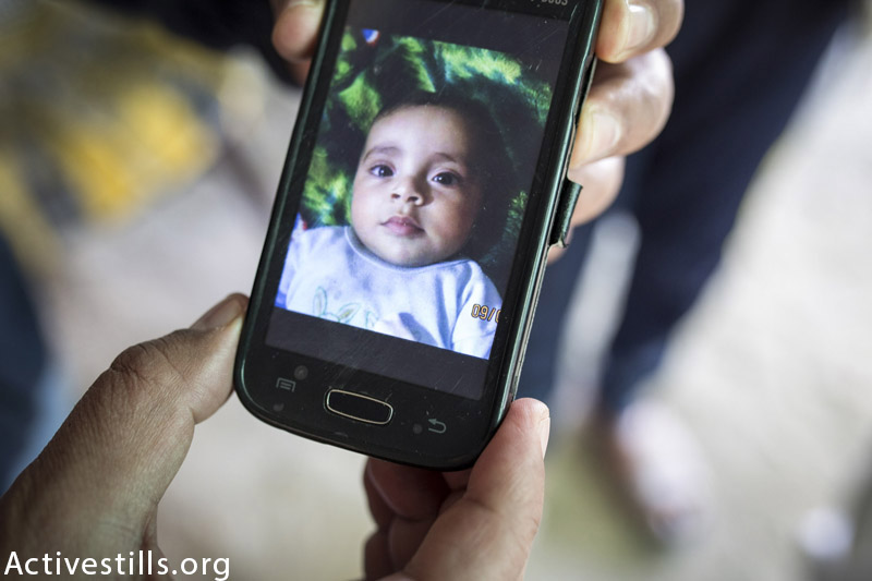 Photo of Abdel Hadi Hayyel Abu Dahrouj (2) on a mobile phone, shown on March 17, 2015 in Al Zawaida village, central Gaza. Abdel was killed on August 23, 2014 together with his entire immediate family — his father Hayyel (28), mother Huda (25) and his brother Abdullah (3). In total five members from the Abu Dahrouj family were killed in the Israeli attack. (Anne Paq / Activestills.org)