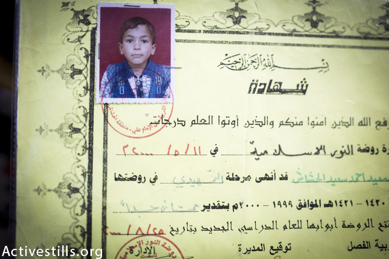 An old photo of Mohammed Al Hashash (at the time of the attack which killed him he was 20) seen on one his school certificates kept by his family in their home in Rafah, Gaza Strip, March 18, 2015. Mohammed was killed together with his four brothers, his mother and one cousin by Israeli attacks on the street when they were fleeing their home, on July 29, 2014. (Anne Paq / Activestills.org)