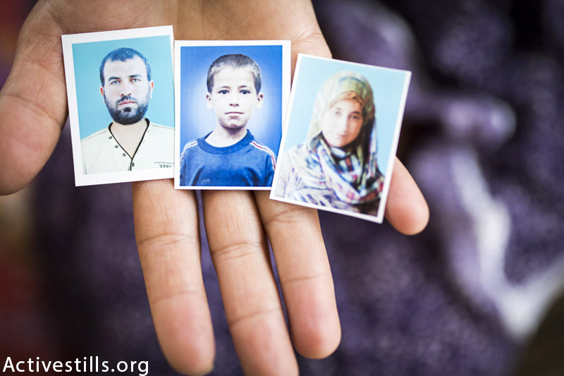 Photos of  Radad Ahmed Tanboura, 36 and his children- Ahmed (15) and Amna (13) held in the hand of their mother and Radad's wife, Elizabeth in the flat the remaining members of the family currently live in Beit Lahiya, Northern Gaza, March 19, 2015. The attack killed the three members of the Tanbura family on August 25, 2014.  Elizabeth was inside the home and was injured in the attack, while the other children were outside and then survived. (Anne Paq / Activestills.org)