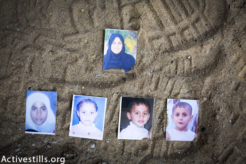 Photos of the members of the Jouda family killed: first row, the mother Rawia (43); and, the second row her children from left to right, Tasneem (14), Raghad (12), Osama (6), and Mohammed Issam Jouda (8), seen on March 19, 2015; on the location of the attack, in the garden in front of their home, in Jabaliya, Gaza Strip. The attack occured on August 24, 2014 by a missile fired from a drone directly on them while they were sitting outside because of the heat. Two children survived, as well as the father. (Anne Paq / Activestills.org)