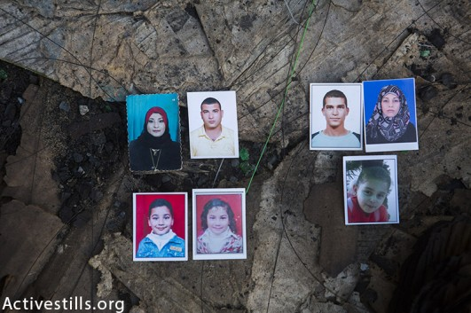 Photos of seven of the 8 members of the Al Khalili family killed, put on the location on the attack, Gaza Strip, November 12, 2014. (Anne Paq / Activestills.org)