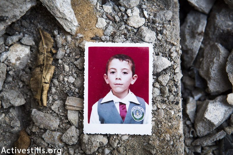 A photograph of Abdallah Abdel Hadi Al Majdalawi(13) in the ruins of his family home, Jabaliya, Gaza Strip, March 19, 2015. Abdallah was killed with two of his brothers and another two cousins during an Israeli attack that destroyed their two homes on August 3rd, 2014. (Anne Paq / Activestills.org)