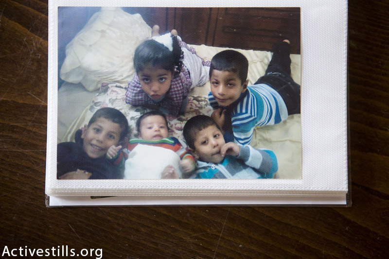 Photos of Nabil Siyam's five children, four of whom died from an Israeli attack on July 21, 2014, seen in the family home, Rafah, Gaza, November 13, 2014. Only Bader (bottom right corner) survived. A total of 13 members from the Siyam family were killed. Around 30 members of the family were fleeing in the street when an Israeli missile hit them. Bader (4) was badly wounded and needed to have his kidney removed, while his father Nabil had his left arm amputated. (Anne Paq / Activestills.org)