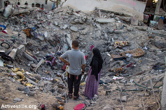 Palestinians standing infront of a crater in Beit Hanoun following bombardment by Israeli forces, North Gaza Strip, August 11, 2014. Till now Israeli attack has killed 1,965 Palestinians, including 1,417 civilians, of whom 458 were children and 238 women. 67 Israelis killed, of whom 64 soldiers, two civilians and one migrant worker. (Anne Paq/Activestills)