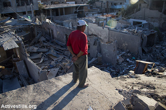 A Palestinian man looking on a destroyed house in Beit Hanoun following bombardment by Israeli forces, North Gaza Strip, August 11, 2014. According to OCHA, 16,800 homes in the Gaza Strip have been destroyed or severely damaged leaving 370,000 displaced. (Anne Paq/Activestills)