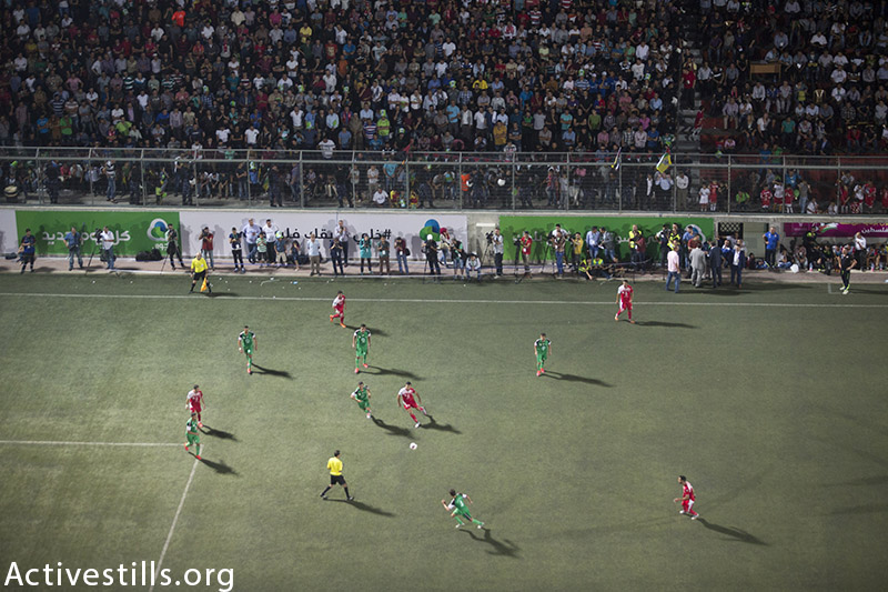 Gaza Strip's Shejaiya's players (green) vie with Hebron's Al-Ahly's players (red) during their return leg football match for the Palestine Cup final, August 14, 2015 at Hussein Bin Ali Stadium in the West Bank city of Hebron.  Hebron's Al-Ahly won 2-1, in the first footballing showdown in 15 years with a team from Israeli-blockaded Gaza to be proclaimed Palestinian champions. Al-Ahly will now represent Palestine, a member of football's world governing body FIFA since 1998, in international competitions. (photo by: Oren Ziv / Activestills.org)