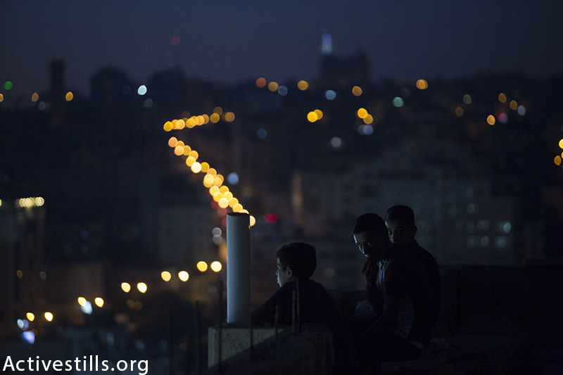 Palestinian youth watch the Palestine Cup final, Hebron, West Bank, August 14, 2015. (photo by: Oren Ziv/Activestills.org)