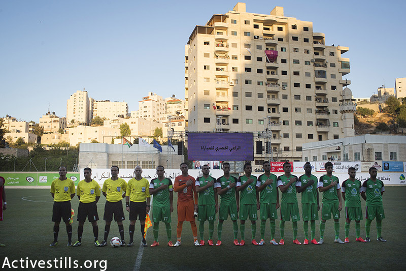 Players from Shejaiya pose for a photo before a football match with Al-Ahly Hebron during the Palestine Cup, August 14, 2015, Hussein Bin Ali Stadium in the West Bank city of Hebron. (photo by: Oren Ziv/Activestills.org)