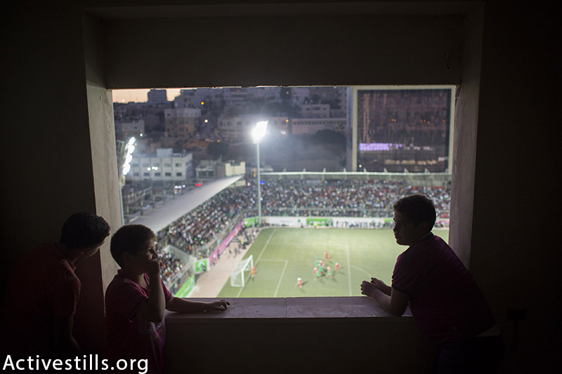 Palestinian boys watch the Palestine Cup final between Gaza's Shejaiya and Hebron's Al-Ahly, August 14, 2015 at Hussein Bin Ali Stadium in the West Bank city of Hebron. (photo by: Oren Ziv/Activestills.org)