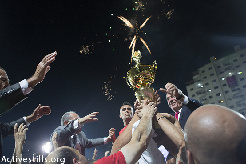 Al Ahly fans and team players celebrate after a football match for the Palestine Cup final between Gaza's Shejaia's club and Hebron's Al-Ahly club on August 14, 2015 at Hussein Bin Ali Stadium in the West Bank city of Hebron.  Hebron's Al-Ahly won 2-1, in the first footballing showdown in 15 years with a team from Israeli-blockaded Gaza to be proclaimed Palestinian champions. Al-Ahly will now represent Palestine, a member of football's world governing body FIFA since 1998, in international competitions. (photo by: Oren Ziv / Activestills.org)