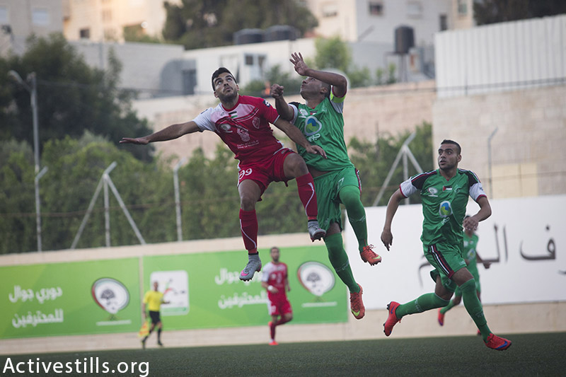 A player from Gaza's Shejaiya's (in green) vies with a player from Al-Ahly (red) during the Palestine Cup final, August 14, 2015 at Hussein Bin Ali Stadium in the West Bank city of Hebron. (photo by: Oren Ziv/Activestills.org)