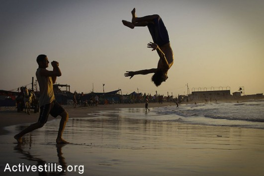 Two young men do acrobatic tricks on Gaza beach, Gaza Strip, September 1, 2013. (Basel Yazouri/Activestills)