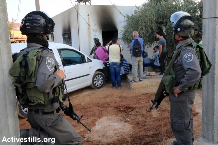 Israeli soldiers are seen in front of the damaged house of the Dawabsha family, which was set on fire by Jewish settlers and where 18-month-old Palestinian toddler Ali Saad Dawabsha died, in the West Bank village of Duma, on July 31, 2015. (Ahmad Al-Bazz/Activestills.org)