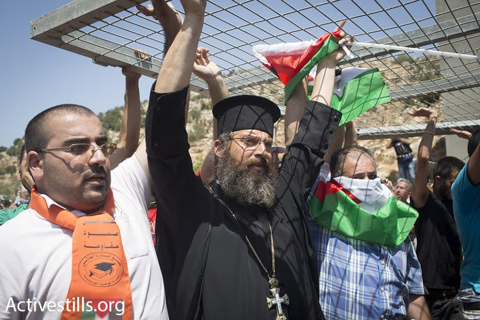 Father Paolo from Beit Jala's Catholic church carries a piece of a checkpoint, during a Muslim-Christian protest against the planned route of the separation barrier, Beit Jala, West Bank, August 23, 2015. (photo: Oren Ziv/Activestills.org)