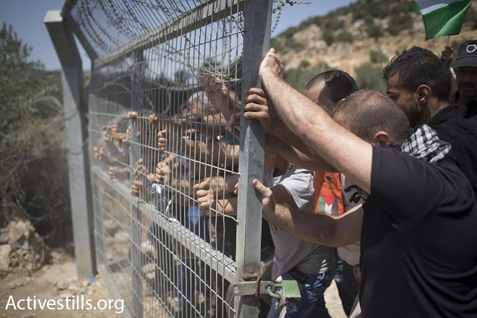 Palestinians try to take apart an Israeli checkpoint in the city of Beit Jala, West Bank, August 23, 2015. (photo: Oren Ziv/Activestills.org)