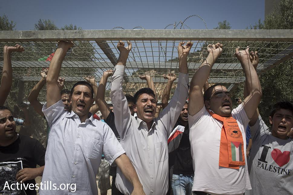 Palestinian demonstrators take apart and carry parts of an Israeli checkpoint during a demonstration against the route of the separation wall, Beit Jala, West Bank, August 23, 2015. (photo: Oren Ziv/Activestills.org)