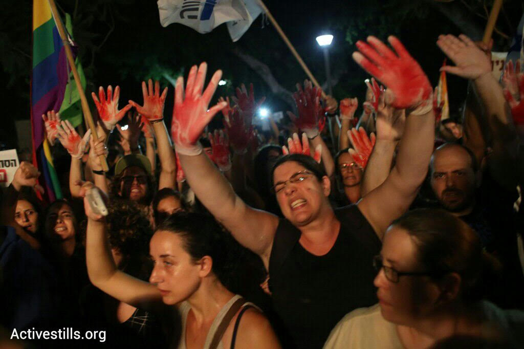 LGBT activists protest Yuval Steinitz as he speaks during a rally protesting the attacks on the Jerusalem Pride Parade, August 1, 2015. (photo: Oren Ziv/Activestills.org)