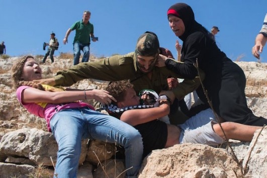 Ahed (left), Nawal (right) and Nariman Tamimi (behind the soldier) try to stop Mohammed, 12, from being arrested by an Israeli soldier at a demonstration in Nabi Saleh, August 28, 2015. (Karam Saleem)