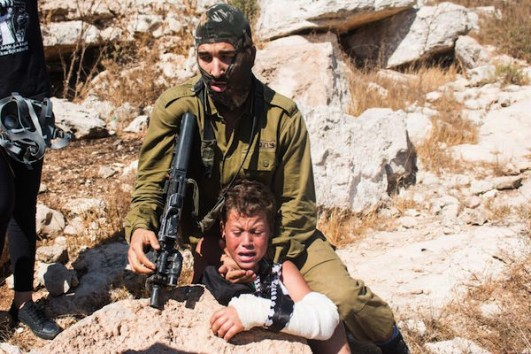 An Israeli soldier holding Mohammed Tamimi, 12, in a headlock during a demonstration in Nabi Saleh, August 28, 2015. (Karam Saleem)