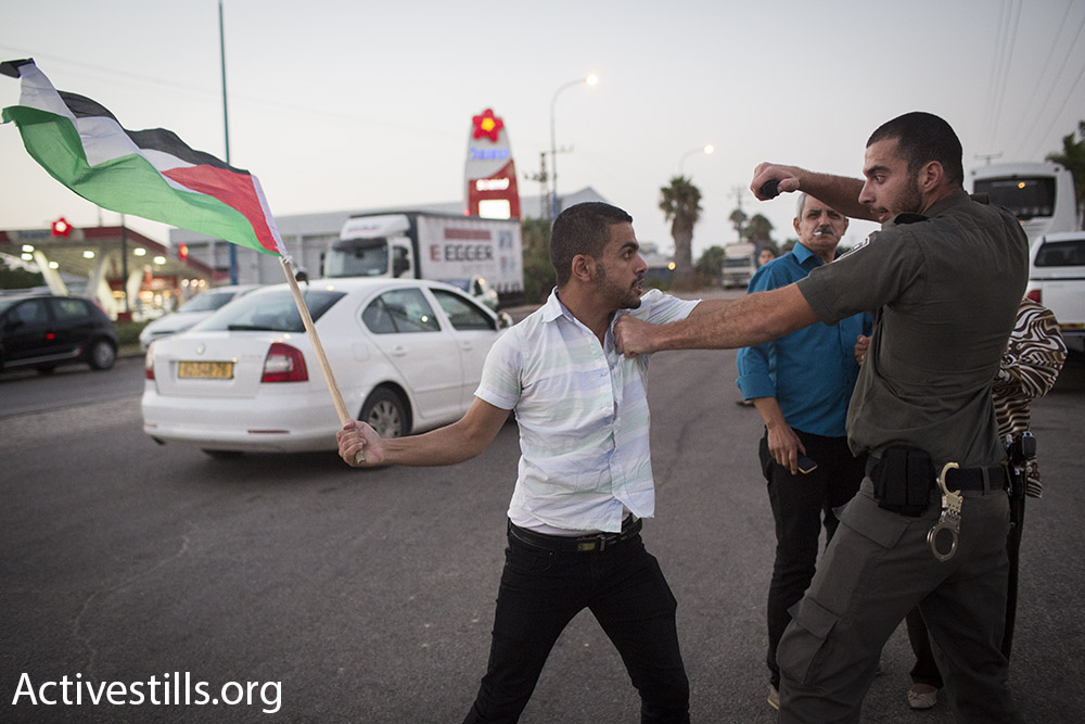 Israeli police clashes with a protester at a demonstration for the release of Palestinian hunger striker Mohammad Allan, outside of Barzilai hospital in Ashkelon, Israel. August 16, 2015. (Oren Ziv/Activestills.org)