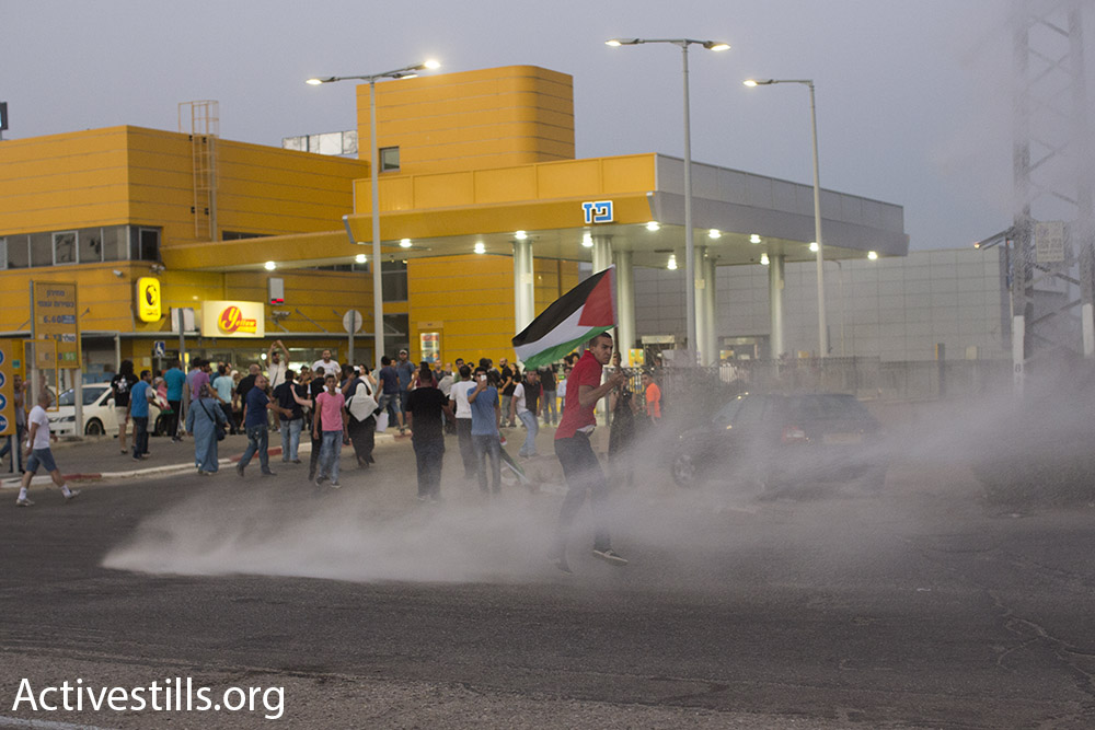 Israeli police sends skunk water cannons toward a protester at a demonstration for the release of Palestinian hunger striker Mohammad Allan, outside of Barzilai hospital in Ashkelon, Israel. August 16, 2015. (Oren Ziv/Activestills.org)