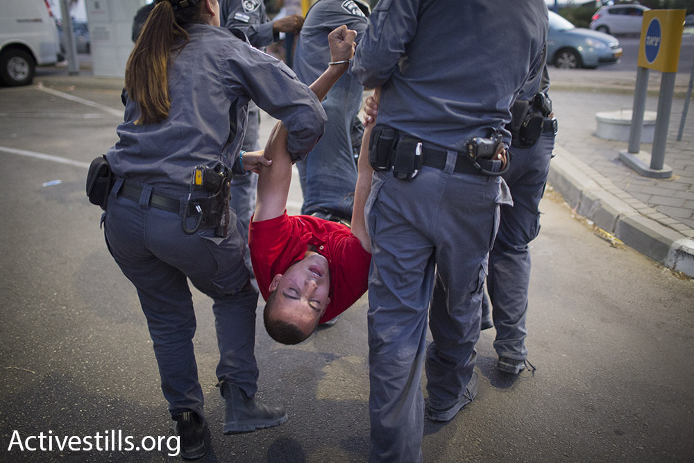 Israeli police detains a protester at a demonstration for the release of Palestinian hunger striker Mohammad Allan, outside of Barzilai hospital in Ashkelon, Israel. August 16, 2015. (Oren Ziv/Activestills.org)