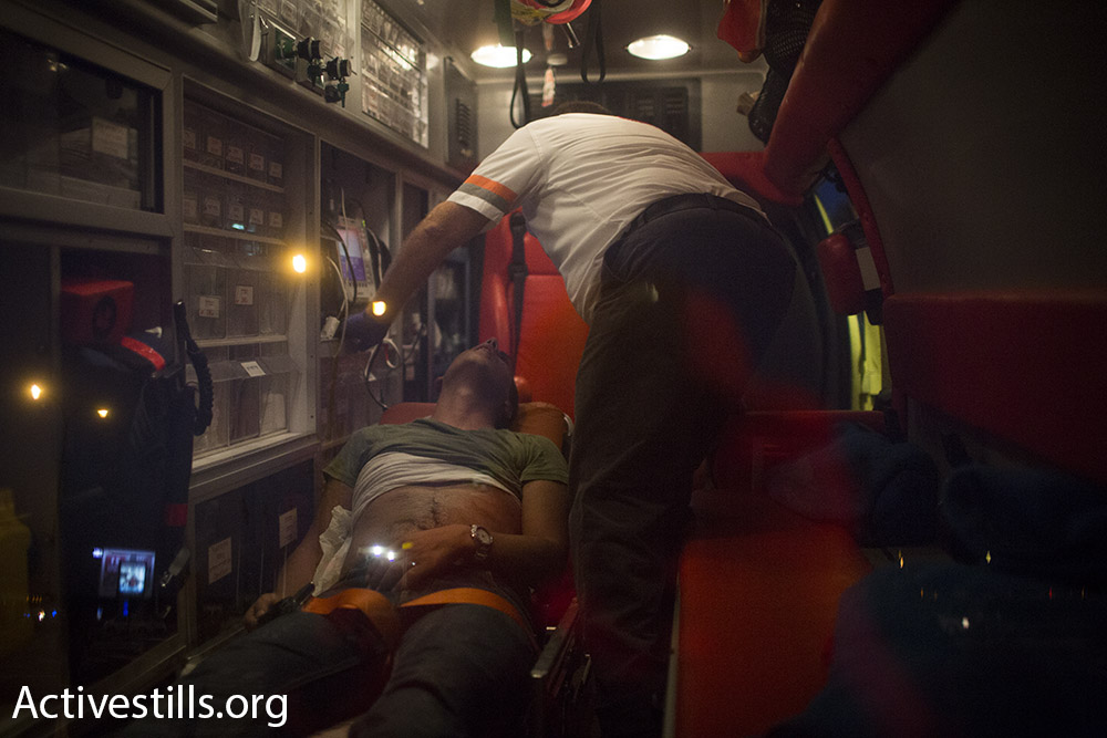 A protestor receives medical care after police attack participants in a demonstration for the release of Palestinian hunger striker Mohammad Allan, outside of Barzilai hospital in Ashkelon, Israel. August 16, 2015. (Oren Ziv/Activestills.org)