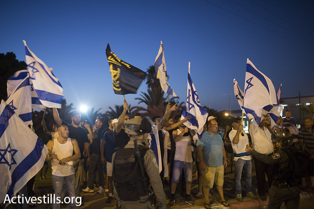 Right-wing protestors demonstrate against the release of Palestinian hunger striker Mohammad Allan, outside of Barzilai hospital in Ashkelon, Israel. August 16, 2015. (Oren Ziv/Activestills.org)