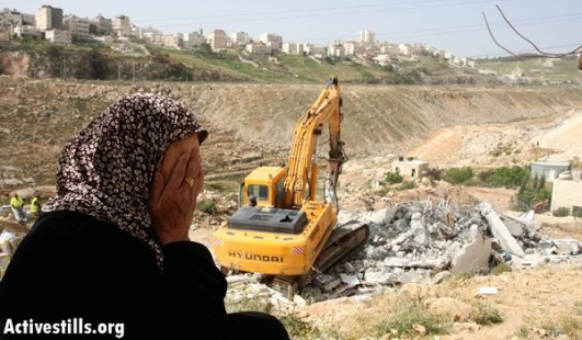House owner weeps while Palestinian contract workers for the city of Jerusalem, demolish her house in Anata, April 14, 2008. (Meged Gozani/Activestills.org