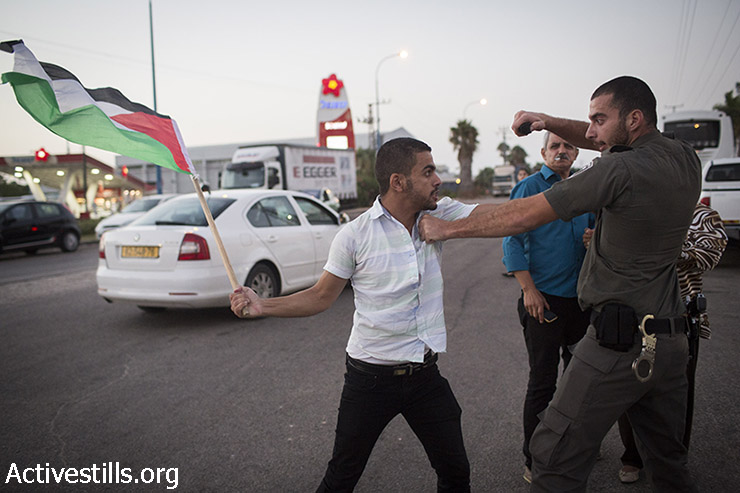 Israeli border policeman points pepper spray towards a Palestinian activist, during a protest for the release of Palestinian Mohammed Allan, who is held by Israel without trial and who has slipped into a coma after a nearly two-month hunger strike, in the city of Ashkelon, August 16, 2015. Police prevented from Palestinian and Israel activists to arrive to the hospital in which Allan is held, arresting eight activists, using pepper spray and skunk water canon. (photo: Oren Ziv / Activestills.org)