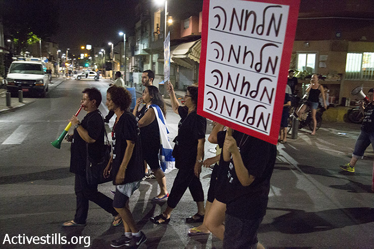"""A resident of south Tel Aviv holds sign read: War, war, war, war"""", during a protest against African asylum seekers. South Tel Aviv residents protest against African asylum seekers, in the south Tel Aviv neighbourhood of Shapira , on August 20, 2015. The protest called against the recent decision of the Israeli supreme court, ordering to jail Asylum seekers in Holot prison for one year, instead on 20 months. (photo: Keren Manor / Activestills.org)"""