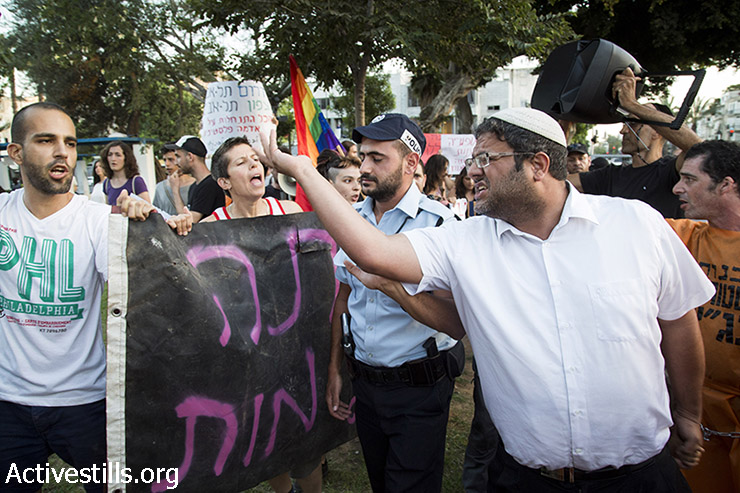 Itam Ben Gvir argue with LGTBQ activists as they protest against homophobia and racism in front of right-wing settlers and a small group of south Tel Aviv residents marching against African asylum seekers, in Levnisky park, South Tel Aviv, August 19, 2015. The right-wing settlers and the south Tel Aviv residents protested against the recent decision of the Israeli supreme court, ordering to jail asylum seekers in Holot Detention Center for one year, instead on 20 months. (photo: Oren Ziv / Activestills.org)