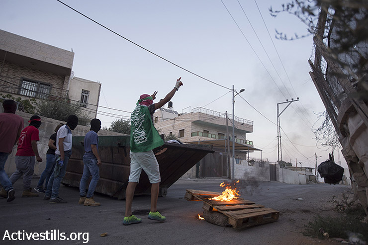 Palestnian youth clash with Israeli police during a protest for the release of Palestinian Mohammed Allan, who is held by Israel without trial and who has slipped into a coma after a nearly two-month hunger strike, in the neighbourhood of Issawiya, East Jerusalem, August 19, 2015. (photo: Fiaz abu-Rmeleh / Activestills.org)