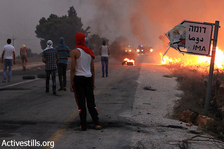 Dozens of Palestinians clash with Israeli forces in Duma village during a protest following the recent Israeli attack on the Dawabsha family, West Bank, August 2, 2015. (photo: Ahmad al-Bazz / Activestills.org)