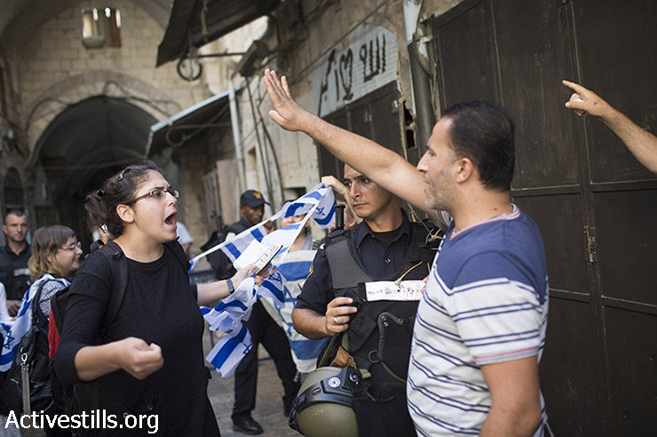 Israeli policeman stands guard as a Palestinian man shouts at Jewish right-wing who demonstrates at one of the entrances to Al-Aqsa mosque compound, in the Old City of Jerusalem, August 9, 2015. (Faiz abu-Rmeleh / Activestills.org)