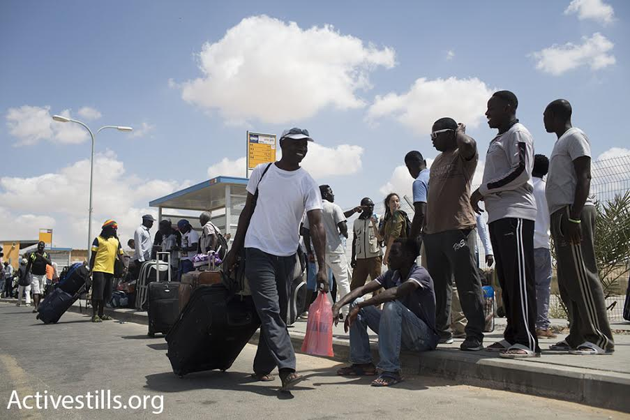 Dozens of asylum seekers wait at a bus stop outside Holot detention center upon being released, August 25, 2015. (photo: Oren Ziv/Activestills.org)